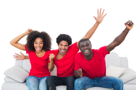 Football fans in red cheering on the sofa on white background photo