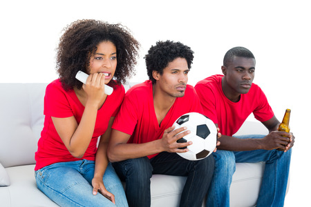 Nervous football fans in red sitting on couch on white background photo