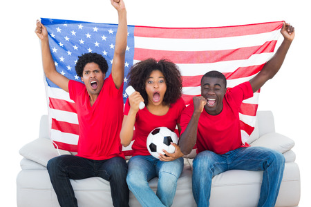 Cheering football fans in red sitting on couch with usa flag on white background photo