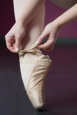 ballet slippers: Ballerina tying the ribbon on her ballet slippers in the ballet studio