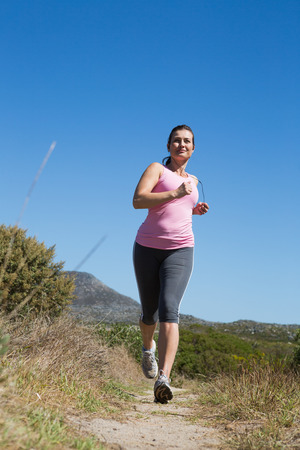 adventuring: Active woman jogging in the countryside on a sunny day