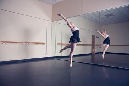 ballet studio: Beautiful ballerina posing in front of mirror in the dance studio
