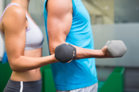 Fit couple lifting dumbbells together at the gym photo