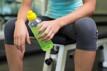 human energy: Fit woman sitting on bench holding energy drink at the gym Stock Photo