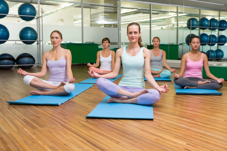Smiling yoga class in lotus pose in fitness studio at the leisure center photo