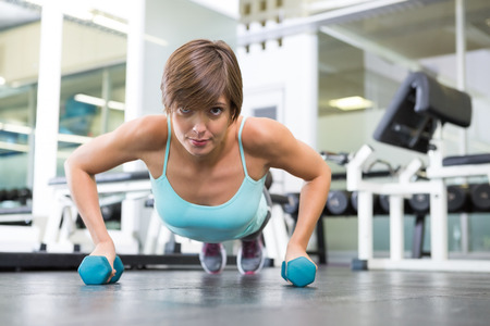 plank position: Fit brunette in plank position with dumbbells at the gym