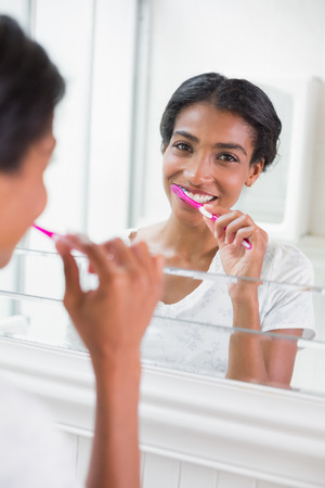 Pretty woman brushing her teeth at home in bathroom photo