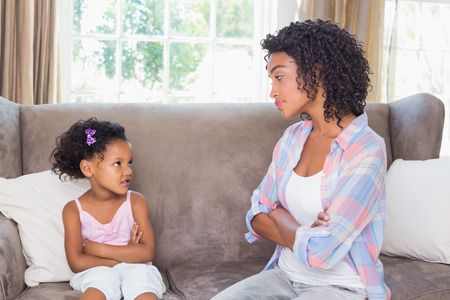 Pretty mother sitting on couch with petulant daughter at home in the living room Stock Photo
