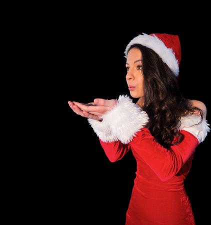 pere noel sexy: Jolie brunette � santa costume soufflant sur ses mains sur fond noir