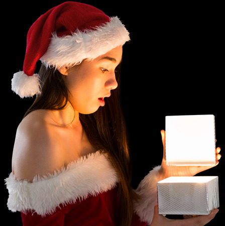 Pretty brunette in santa outfit opening a gift on black background photo