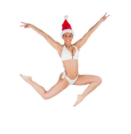 wearing santa hat: Fit girl in bikini smiling at camera wearing santa hat on white background Stock Photo