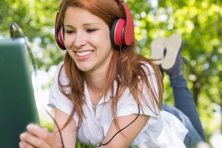 Pretty redhead using her tablet pc while listening to music in the park  on a sunny day photo