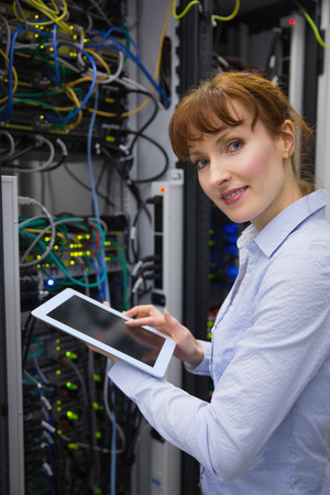 Smiling technician using tablet pc while analysing server in large data center photo