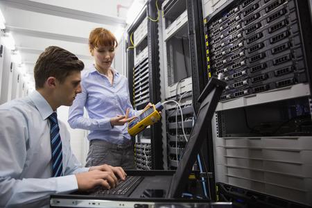 Team van technici met behulp van digitale kabel-analyser op servers in grote datacenter