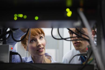 computer centre: El equipo de t�cnicos hablando y mirando servidor en gran centro de datos