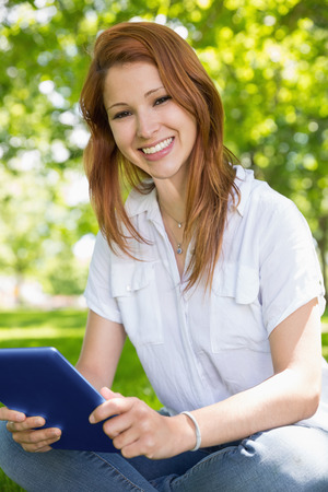 Pretty redhead using her tablet pc in the park on a sunny day photo