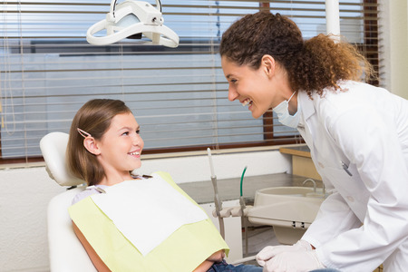Pediatric dentist examining little girls teeth in the dentists chair at the dental clinic photo
