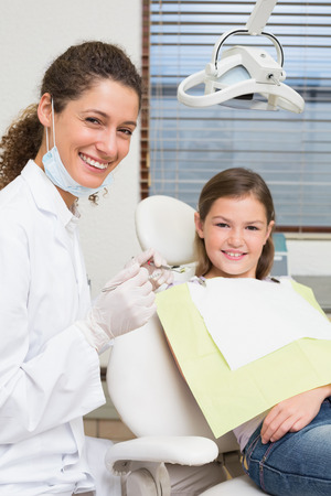 Pediatric dentist and little girl in the dentists chair smiling at camera at the dental clinic photo