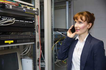 computer server: Pretty computer technician talking on phone beside open server in large data center Stock Photo