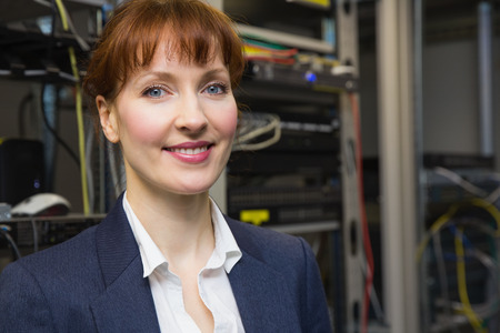 Pretty computer technician smiling at camera beside open server in large data center photo