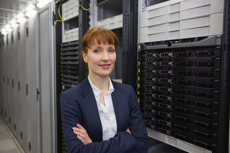 computer server: Pretty technician smiling at camera beside server tower in large data center Stock Photo