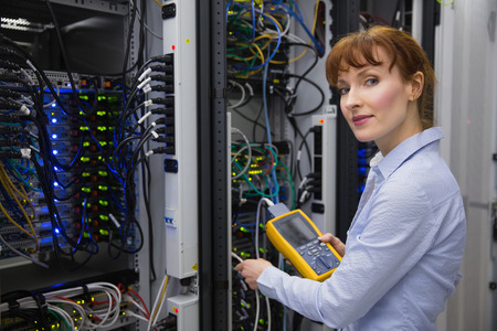 technician: Technician using digital cable analyzer on server in large data center
