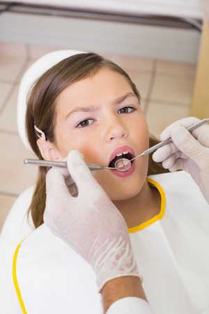 Pediatric dentist examining a patients teeth in the dentists chair at the dental clinic