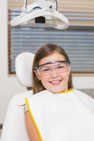 Little girl sitting in dentists chair wearing protective glasses at the dental clinic photo