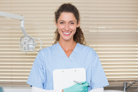 Dentist in blue scrubs holding clipboard at the dental clinic photo