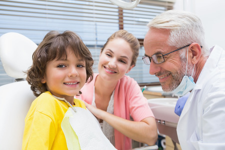Little boy smiling at camera with mother and dentist beside him at the dental clinic photo