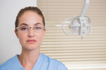 Dentist in blue scrubs looking at camera at the dental clinic