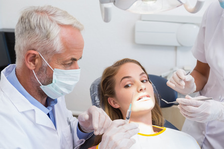 Dentist examining a patients teeth in the dentists chair with assistant at the dental clinic photo