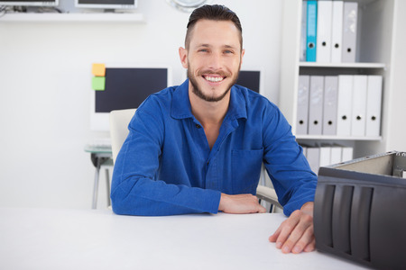 it technician: Computer engineer sitting at desk smiling at camera in his office