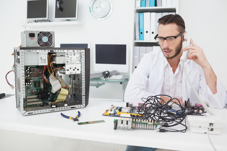 Computer engineer looking at broken device and making a phone call in his office photo