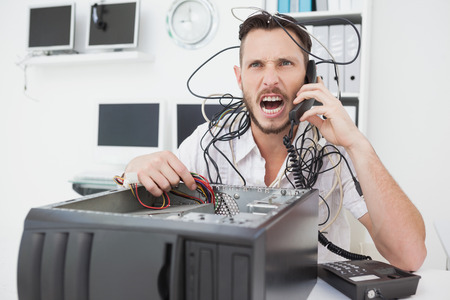 Angry computer engineer making a call in his office photo