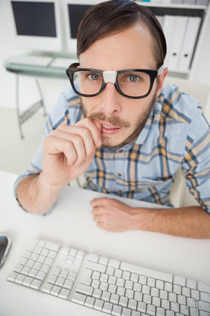 businessman working at his computer: Nerdy nervous businessman working on computer in his office