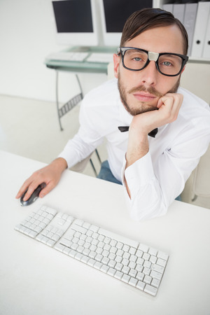 businessman working at his computer: Nerdy bored businessman working on computer  in his office