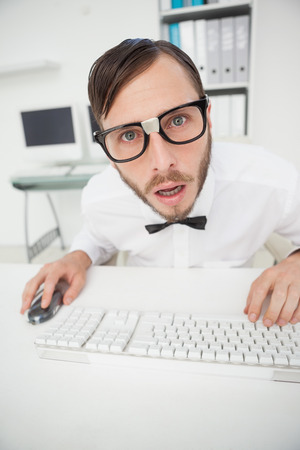 businessman working at his computer: Nerdy shocked businessman working on computer  in his office