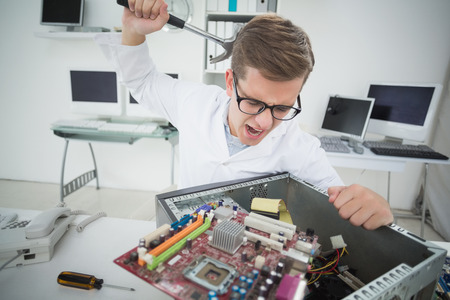 Computer engineer holding hammer over broken console in his office photo