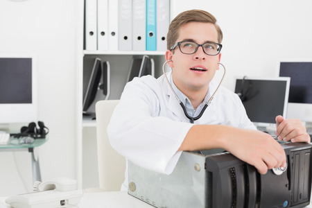 Computer engineer listening to console with stethoscope in his office photo
