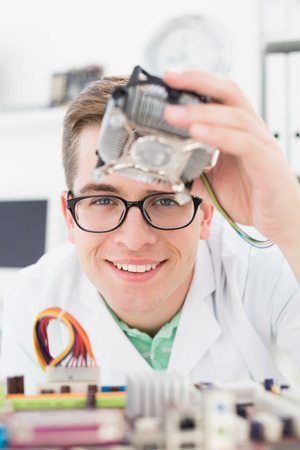 Smiling technician working on broken cpu in his office photo