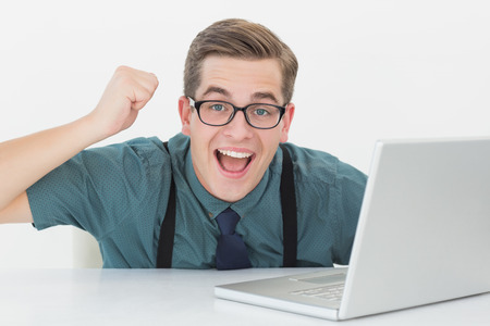 Nerdy businessman at his desk looking at laptop in his office photo