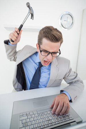 Angry businessman holding hammer over laptop in his office photo