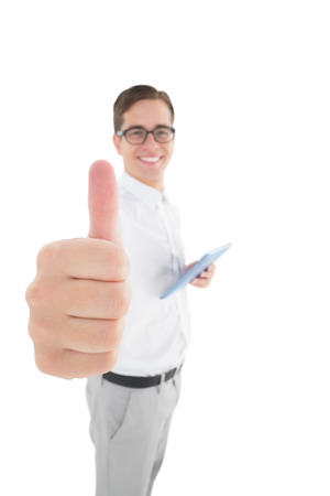 Nerdy businessman holding his digital tablet showing thumbs up on white background photo