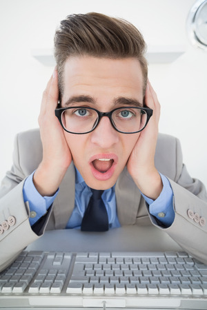businessman working at his computer: Shocked businessman working on computer in his office