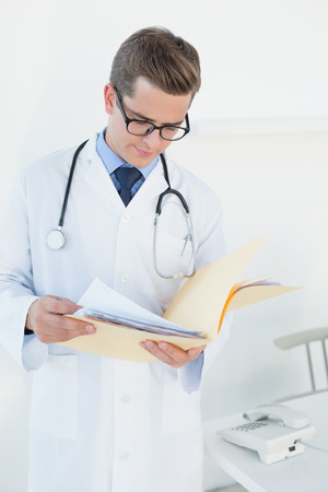 Young handsome doctor reading file in his office photo