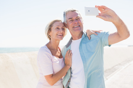 chinos: Happy senior couple posing for a selfie on a sunny day