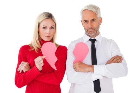 Couple not talking holding two halves of broken heart on white background photo