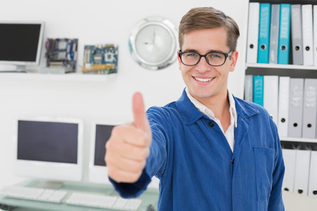 Smiling technician looking at camera showing thumbs up in his office 版權商用圖片 - 31310641