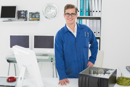 boiler suit: Smiling technician looking at camera in his office